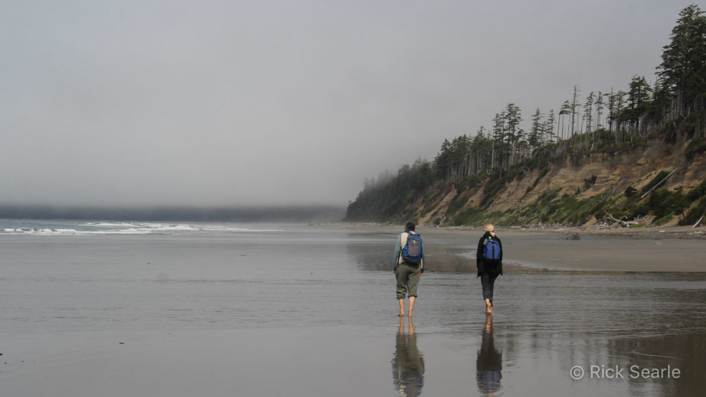 Two Hikers on Sandy Beach